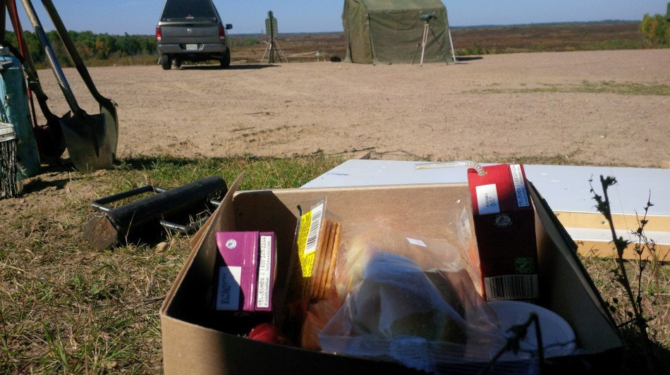 Box with juiceboxes and crackers on background of field, truck, and tent