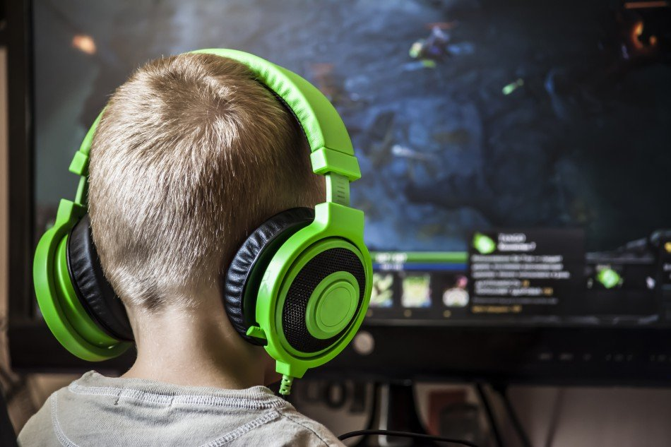 Little boy playing video game with headphones on