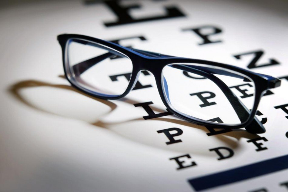 Pair of glasses resting on an optometrist's Letter Screen