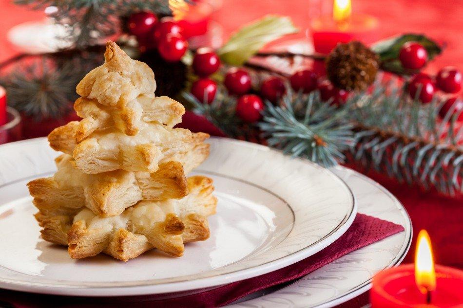Christmas pastry on plate with holly and pine in background