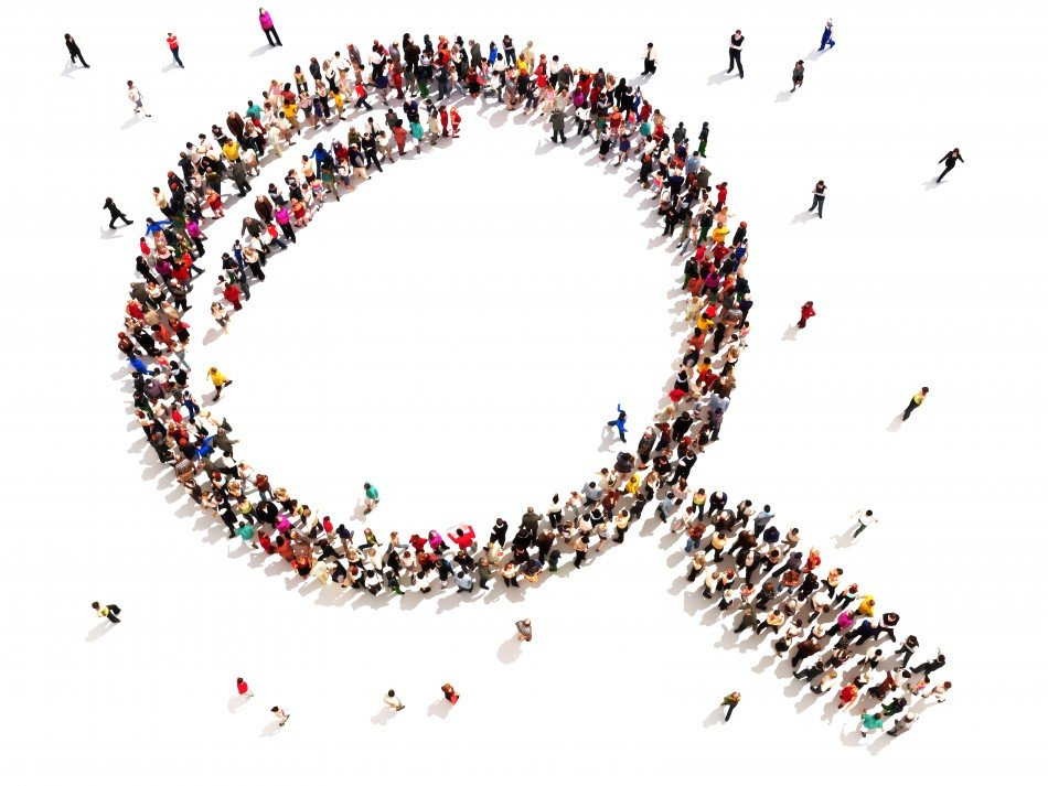 Group of people that have created a large scale image of a magnifying glass